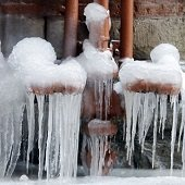 a water meter with icicles hanging from it