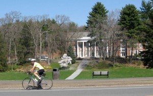 A bicyclist rides by the Town Hall and the Town Green
