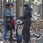 2 women using a log splitter for firewood