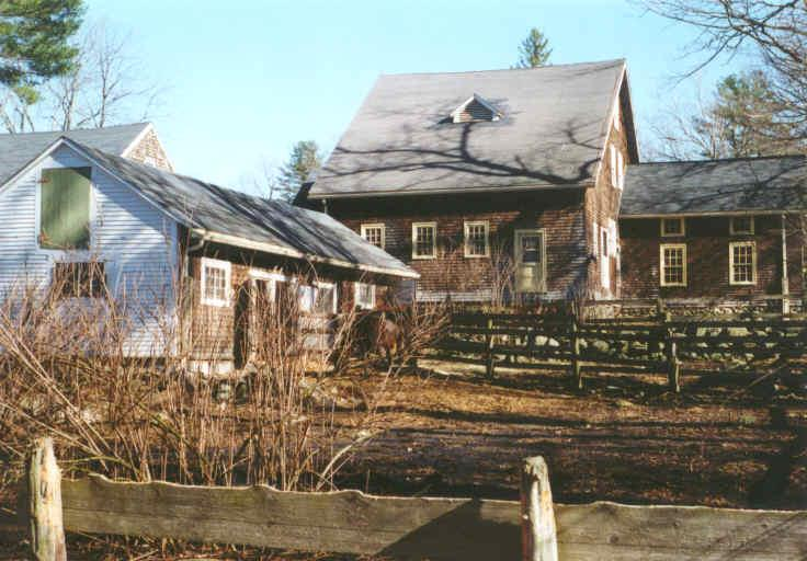 A brown house with a matching outbuilding