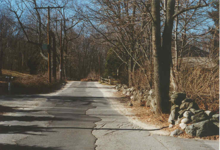 A road with a stone wall beside it