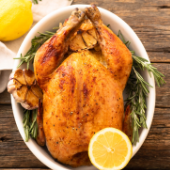 birds eye view of roasted chicken with rosemary and a half lemon on wooden table