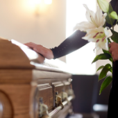 person holding flowers with their hand on top of a casket