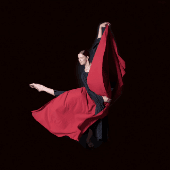 woman wearing black leotard dancing with red billowing material on a black background