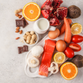 birds-eye photograph of allergen foods: oranges, chocolate, peanuts, nuts, eggs, pomegranate, mushrooms, milk